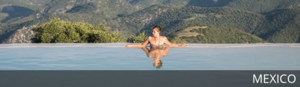 Woman sits in natural spa against mountains at Hierve el Agua in Mexico. With text overlay: Mexico