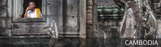 Man blows a kiss at the Angkor Wat temples in Cambodia with text overlay: Cambodia