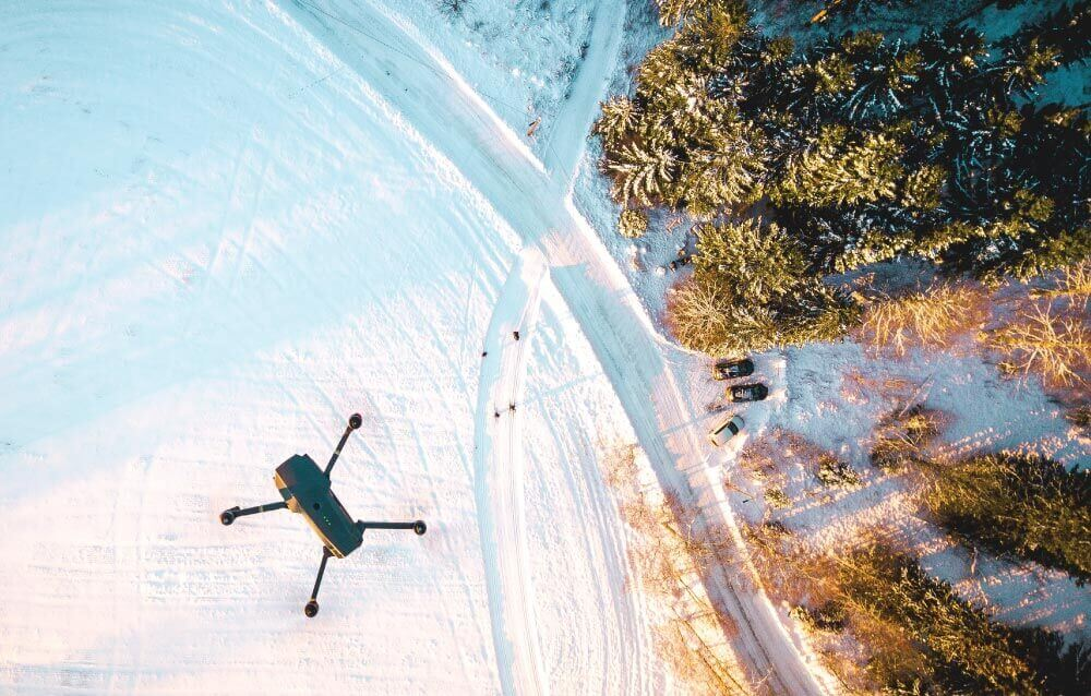 A drone flying above snow for the post: The Best Travel Drones