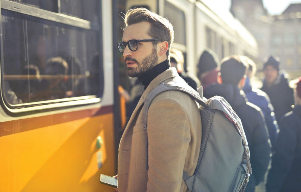 Man waits at busy train station wearing an anti theft backpack for travel