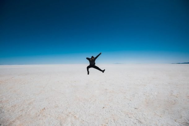 Man jumps on Bolivian salt flats for How to save money for long-term travel