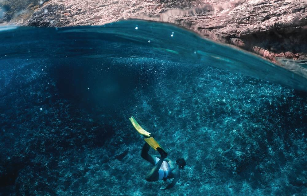 10 of the Best Snorkel Fins for Travel - our Top Snorkeling Fins Reviews- a snorkeler dives to the bottom