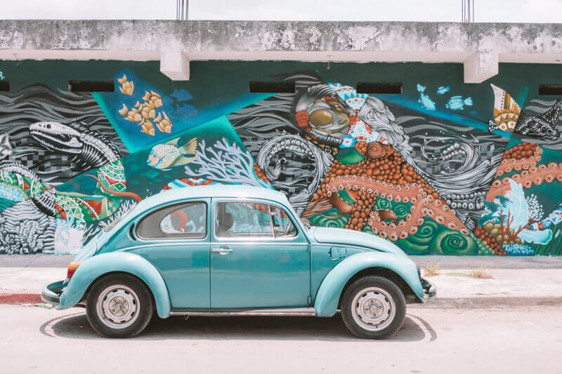A beetle car in front of graffiti - Driving in Mexico Road Trip