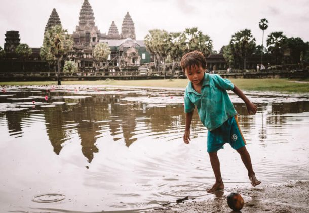 Boy plays soccer with a coconut in front of the Angkor Wat temples for the Backpacking Cambodia Itinerary