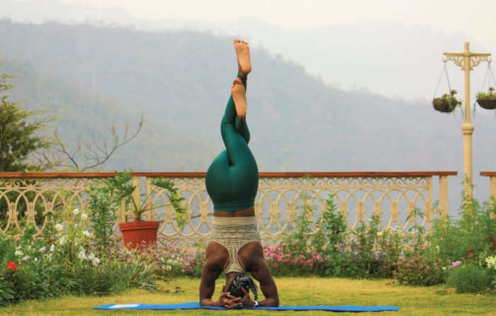 Woman does headstand on a travel yoga mat with a viewpoint for post Traveling with a yoga mat
