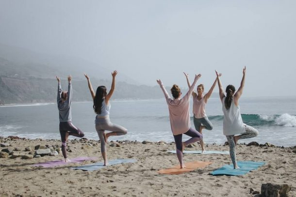 People doing yoga on a beach for Traveling With A Yoga Mat post