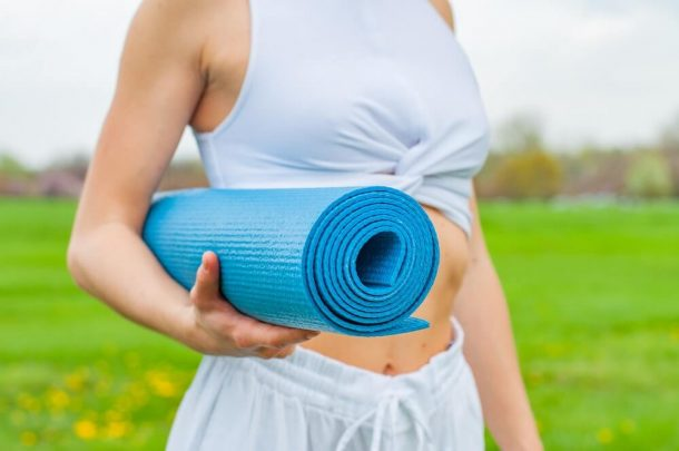 Rolled up blue yoga mat in someones arms for Traveling With A Yoga Mat post