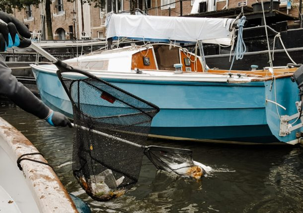 Scooping plastic out of the canals is a unusual and weird things to do in Amsterdam